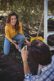 Freund, der lächelnde Freundin am olivgrünen Bauernhof fotografiert Stockbilder