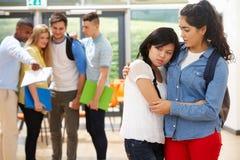 Freund, der Opfer von in der Schule einschüchtern tröstet Lizenzfreie Stockbilder