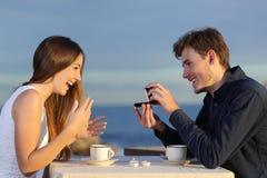 Freund, der um Hand seiner Freundin mit einem Verlobungsring bittet lizenzfreies stockfoto