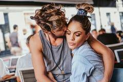 Freund, der verärgerte Freundin in einem Café küsst lizenzfreies stockfoto