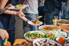 Freund-Glück, das Dinning Essenkonzept genießt Lebensmittelbuffet Versorgendes Speisen Essen der Partei Teilen des Konzeptes Stockfotos