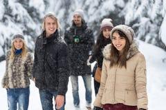 Freund-Gruppen-Schnee-Forest Happy Smiling Young People-Gehen im Freien lizenzfreie stockfotografie