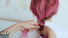 Freund macht dem Mädchen mit dem rosa Haar Zopf stock video footage