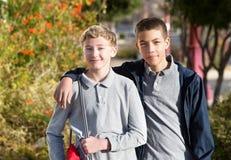 Freund mit dem Arm um Schulkameraden Stockfotos