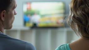 Freund und Freundin aufpassendes Fernsehen zu Hause, Kanäle schaltend, hintere Ansicht stock footage
