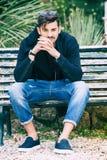 Freundaufwartung Hübsches vorbildliches Sitzen des jungen Mannes auf der Bank Stockfotografie