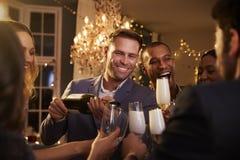 Freunde öffnen Champagne As They Celebrate At-Partei zusammen Stockbilder
