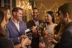 Freunde öffnen Champagne As They Celebrate At-Partei zusammen Lizenzfreie Stockfotos