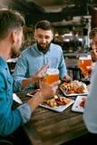 Freunde an Abendessen-trinkendem Bier und Lebensmittel am Restaurant an essen stockfotos
