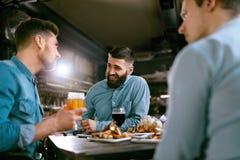 Freunde an Abendessen-trinkendem Bier und Lebensmittel am Restaurant an essen stockfotografie