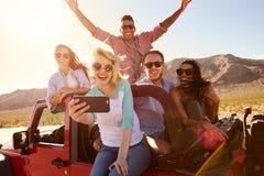 Freunde auf Autoreise im konvertierbaren Auto, das Selfie nimmt lizenzfreie stockfotos
