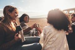 Freunde auf der Autoreise, die sich draußen entspannen und trinkendem Kaffee lizenzfreies stockbild
