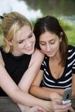 Freunde auf Handy zusammen (schöne junge Blondine und Brune Lizenzfreies Stockfoto
