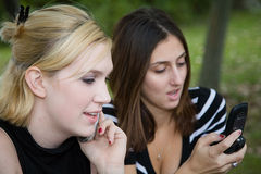 Freunde auf Handy zusammen (schöne junge Blondine und Brune Lizenzfreies Stockbild