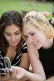 Freunde auf Handy zusammen (schöne junge Blondine und Brune Stockfotografie