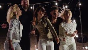 Freunde auf Jugendspaßpartei haben Spaß und Tanzen auf Nachtstrand auf Hintergrund des Dekors mit Lampen stock video footage