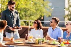 Freunde an bbq-Partei auf Dachspitze im Sommer lizenzfreie stockbilder
