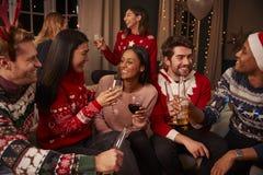 Freunde in den festlichen Pullovern feiern am Weihnachtsfest lizenzfreie stockfotografie