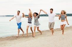 Freunde in der gestreiften Kleidung, die entlang Strand läuft stockfotos