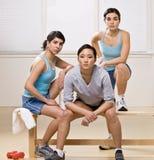 Freunde in der Sportkleidung, die auf Bank sitzt Stockfotografie