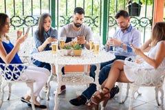 Freunde, die über ihren Smartphones überprüfen Stockfotos