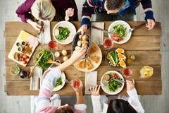 Freunde, die am Abendtische essen stockbild