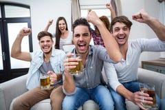 Freunde, die Alkohol beim Aufpassen des Fußballspiels zujubeln und trinken stockfoto