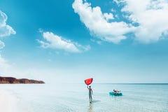 Freunde, die auf aufblasbarem Ring auf dem Strand sich entspannen stockbilder