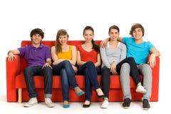 Freunde, die auf Couch sitzen Stockbild
