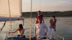 Freunde, die auf der Yacht bei Sonnenuntergang sich entspannen stock footage