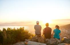 Freunde, die auf einem Gebirgspfad aufpasst das Sonnenaufgang togethe sitzen stockbilder