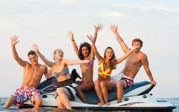 Freunde, die auf einem Jet-Ski sitzen Lizenzfreie Stockfotos