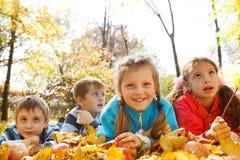 Freunde, die auf gelben Blättern liegen Stockfoto