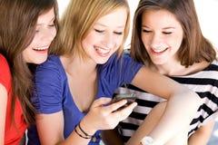 Freunde, die auf Mobiltelefon schauen Stockfotografie