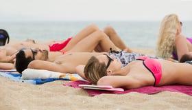 Freunde, die auf Sand am Strand legen Stockfotografie