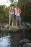 Freunde, die auf Steinen durch Fluss stehen Stockbild