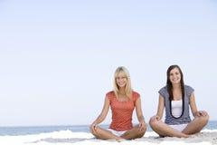 Freunde, die auf Strand sich entspannen stockfotografie