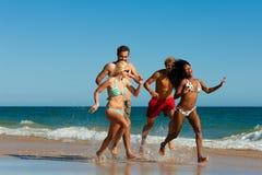 Freunde, die auf Strandferien laufen Stockbild