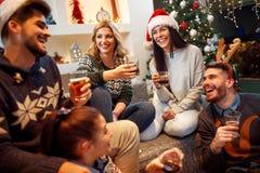 Freunde, die auf Weihnachtsfest lachen lizenzfreie stockbilder