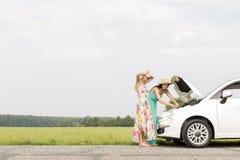 Freunde, die aufgegliedertes Auto auf Landstraße gegen klaren Himmel überprüfen stockbild