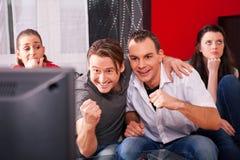 Freunde, die aufregendes Spiel an Fernsehapparat überwachen Stockbilder