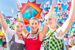 Freunde, die bayerisches angemessenes besuchen, Spaß am Karussell habend Stockfotos