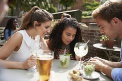 Freunde, die bei Tisch im Kneipen-Garten betrachtet Mitteilung am Handy sitzen lizenzfreie stockfotografie