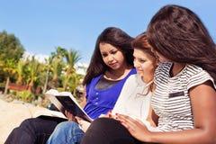 Freunde, die Bibel auf dem Strand lesen stockbild
