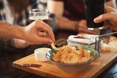 Freunde, die Bier trinken und bei Tisch Snäcke essen Stockbild