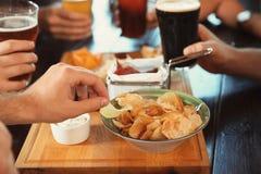 Freunde, die Bier trinken und bei Tisch Snäcke essen Lizenzfreie Stockbilder