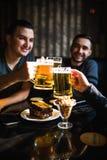 Freunde, die Bier trinken und Gläser an der Bar oder an der Kneipe klirren Lizenzfreies Stockbild