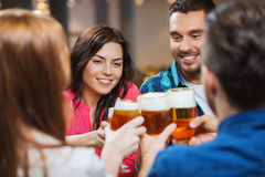 Freunde, die Bier trinken und Gläser an der Kneipe klirren Stockbild
