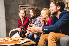 Freunde, die Bier trinken und Pizza essen Stockbild