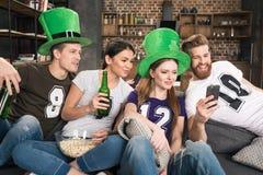 Freunde, die Bier trinken und Smartphone verwenden Stockfotos
